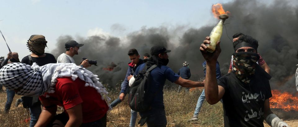 A demonstrator holds a Molotov cocktail during clashes with Israeli troops at a protest where Palestinians demand the right to return to their homeland, at the Israel-Gaza border in the southern Gaza Strip, April 27, 2018. REUTERS/Ibraheem Abu Mustafa