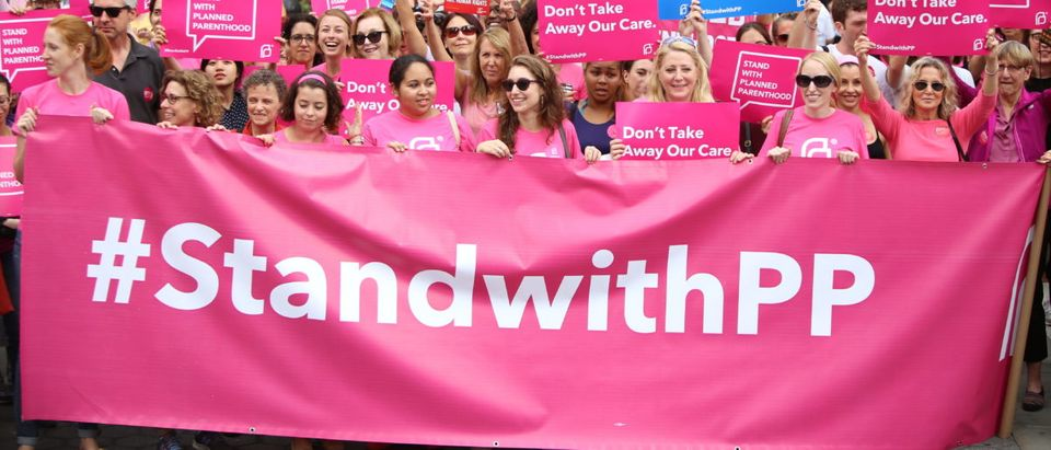 Planned Parenthood activists hold a sign. (Shutterstock/a Katz)