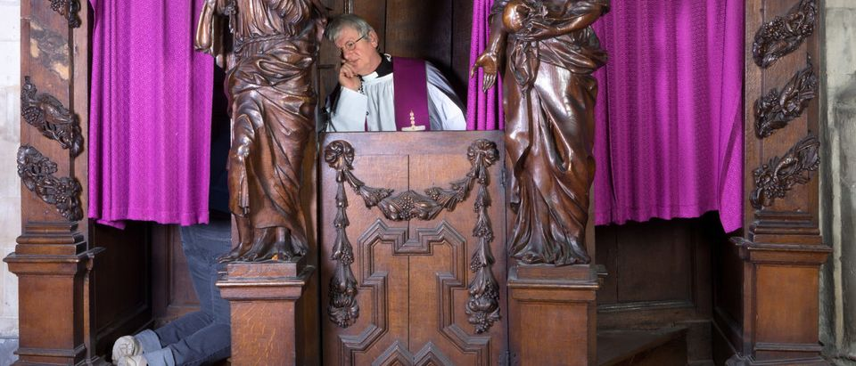 Priest Hearing Confession (Shutterstock/ Anneka)