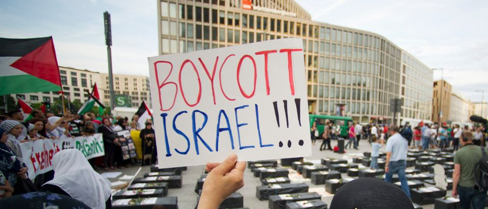 "A woman holds a sign which reads ""Boycott Israel"" in front of symbolic coffins while attending a demonstration supporting Palestine, in Berlin"