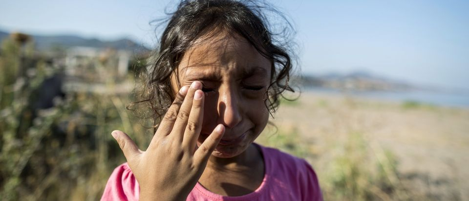 Yasmine, a 6-year-old migrant from Deir Al Zour in war-torn Syria, cries at the beach after arriving on the Greek island of Lesbos