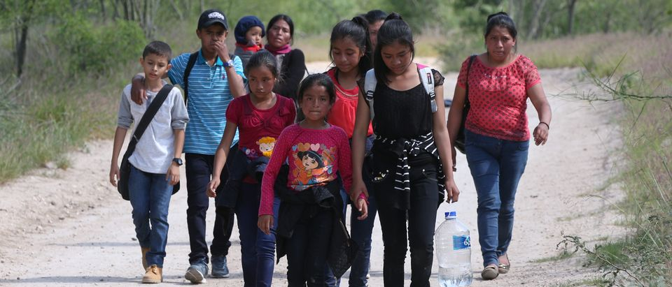 People who illegally crossed the Mexico-U.S. border walk up a dirt road near McAllen