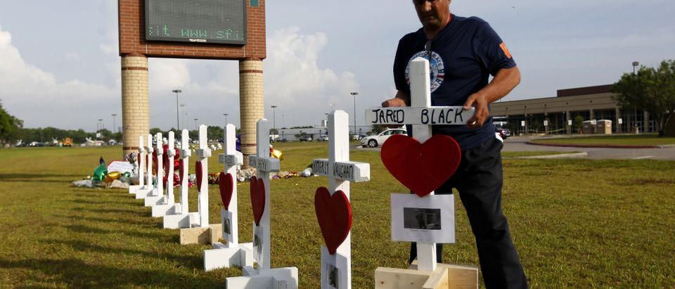 Greg Zanis places crosses bearing the names of the victims killed in a shooting at Santa Fe High School in Santa Fe