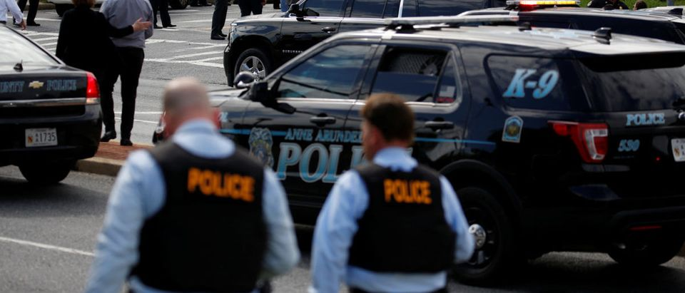 Law enforcement officials survey the scene after a gunman fired through a glass door at the Capital Gazette newspaper and sprayed the newsroom with gunfire, killing at least five people and injuring several others, in Annapolis, Maryland, U.S., June 28, 2018. REUTERS/Joshua Roberts