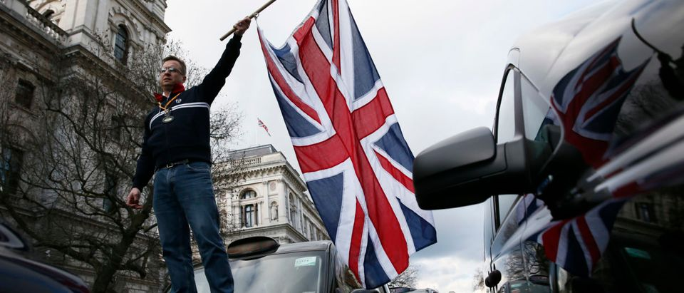 A London cab driver waves a Union flag as he stands on the bonnet of his taxi during a protest against Uber on Whitehall in central London, February 10, 2015 REUTERS/Stefan Wermuth