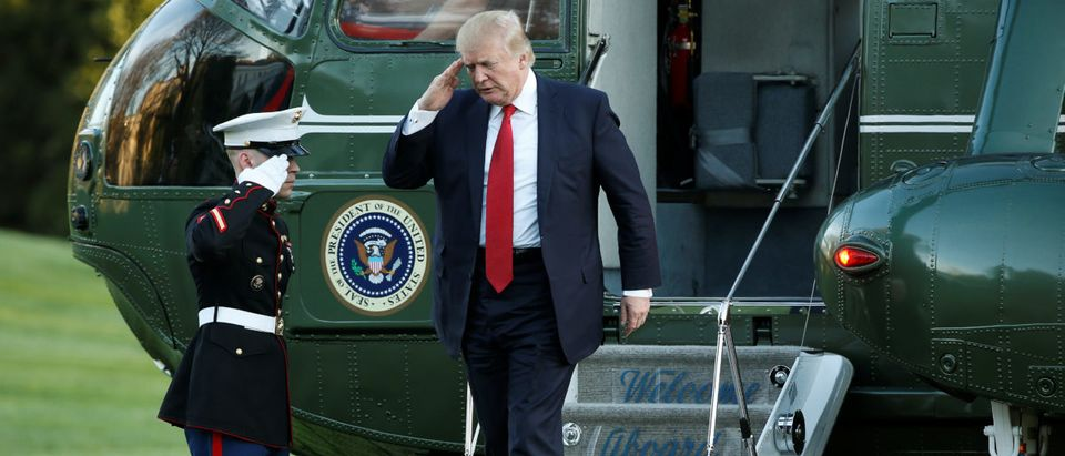 U.S. President Donald Trump salutes a Marine as he walks from Marine One upon his return to the White House in Washington