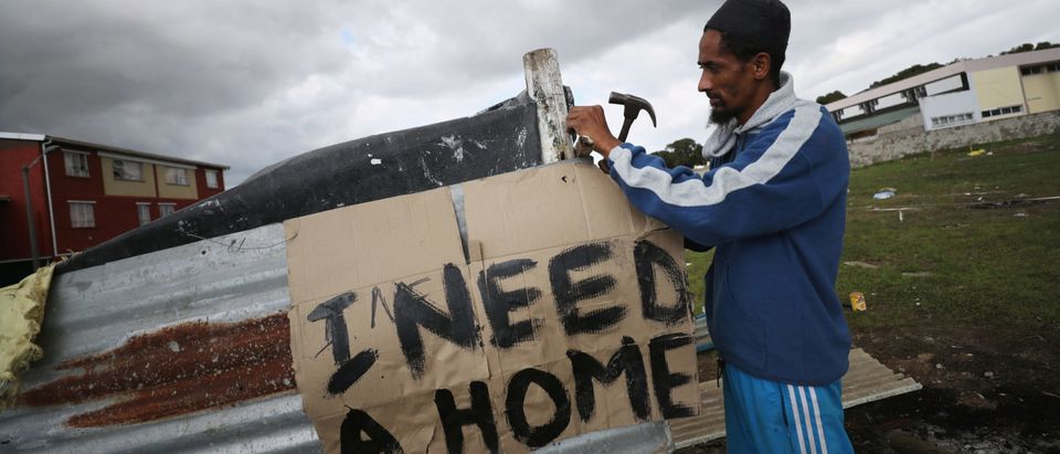 Father of seven, Muneer Baxter, works on a shack erected during illegal land occupations, in Mitchell's Plain township near Cape Town