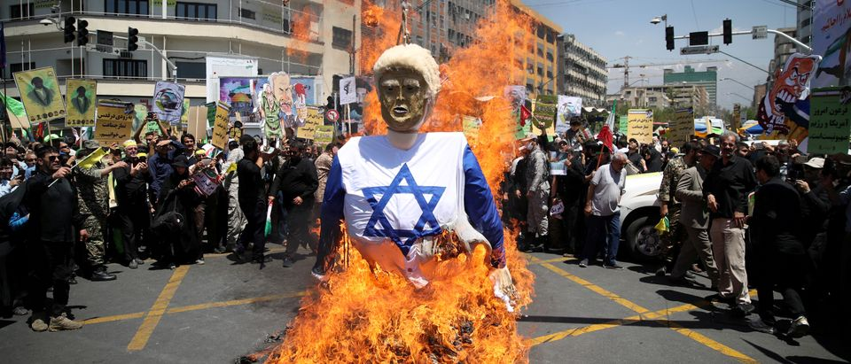Iranians burn an effigy in the likeness of U.S. President Donald Trump during a protest marking the annual al-Quds Day (Jerusalem Day) on the last Friday of the holy month of Ramadan in Tehran, Iran June 8, 2018. Tasnim News Agency/via REUTERS