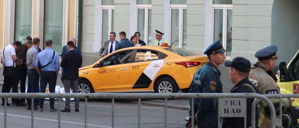 Investigators and members of emergencies services gather near a damaged taxi, which ran into a crowd of people, is evacuated in central Moscow