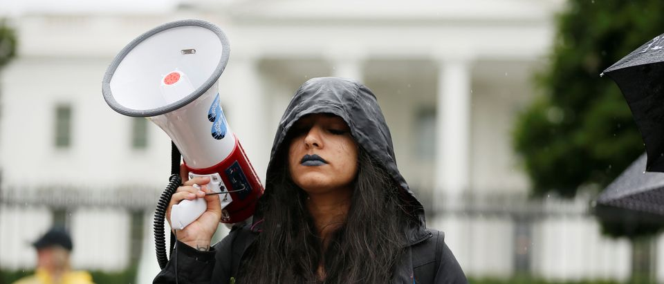 Protestor closes her eyes as she listens to cries of detained children separated from their parents during a demonstration outside White House in Washington