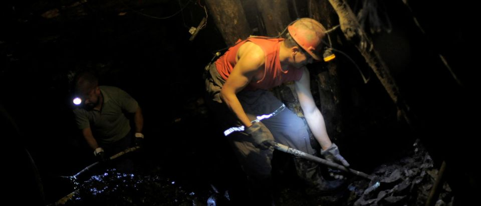 """Coal miners use shovels to remove coal from inside an old artisanal coal mine, so called """"Pique"""", in Curanilahue"""