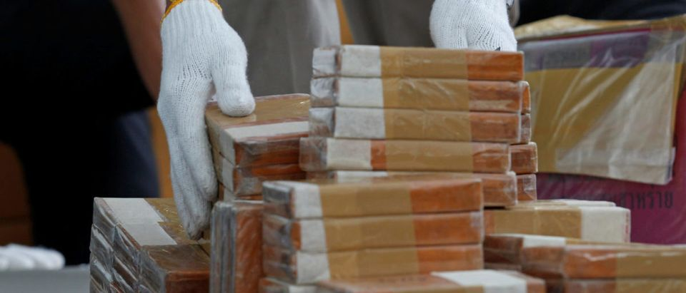 A Thai narcotics official arranges bags of heroin before the 46th Destruction of Confiscated Narcotics ceremony in Ayutthaya province