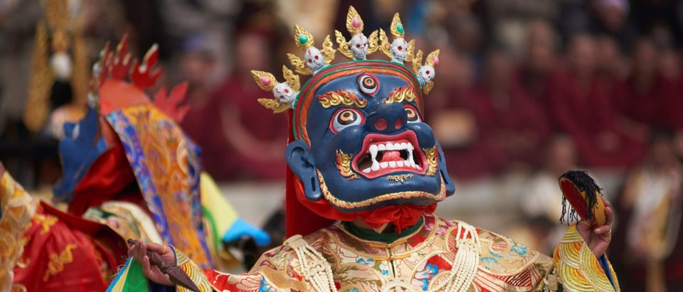 Tibetan monks perform a ritual dance as they attend a celebration event during Tibetan New Year festival in Zhuoni county, Gannan