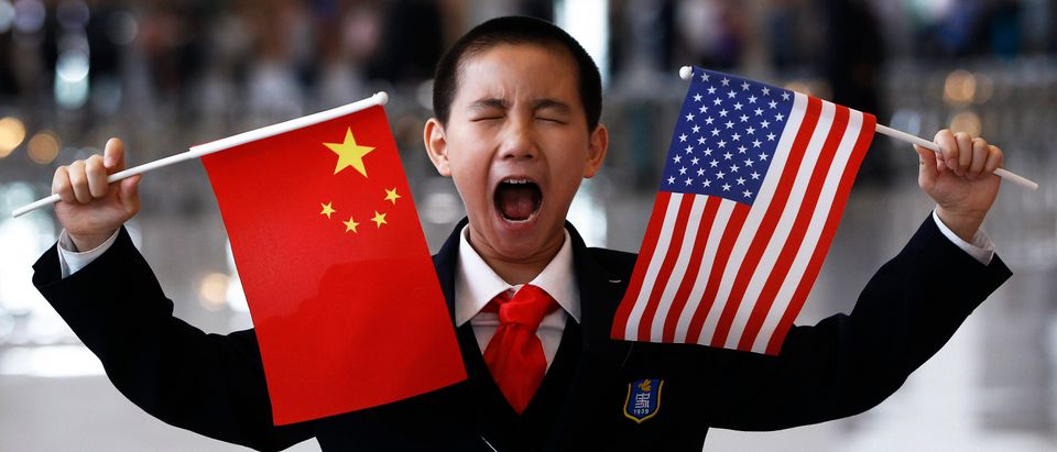 A boy who is waiting to greet U.S. Secretary of State Hillary Clinton at the National Museum makes a face while holding the U.S. and Chinese flags in Beijing May 4, 2012. REUTERS/Shannon Stapleton (CHINA - Tags: POLITICS BUSINESS TPX IMAGES OF THE DAY) - GM1E8541BEV01