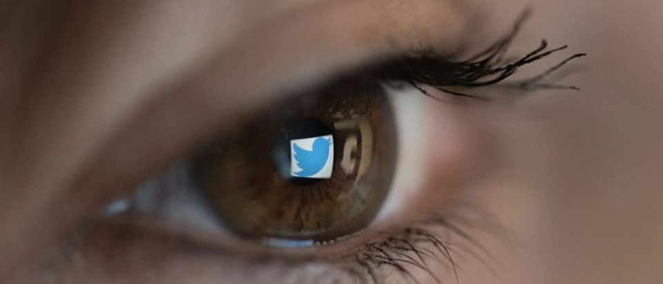 An illustration picture taken on March 22, 2018 in Paris shows a close-up of the Twitter logo in the eye of an AFP staff member posing while she looks at a flipped logo of Twitter. (Photo credit should read CHRISTOPHE SIMON/AFP/Getty Images)