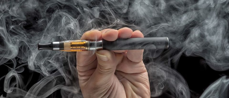 Hand holding an electronic cigarette over a dark background. Oleg GawriloFF/Shutterstock