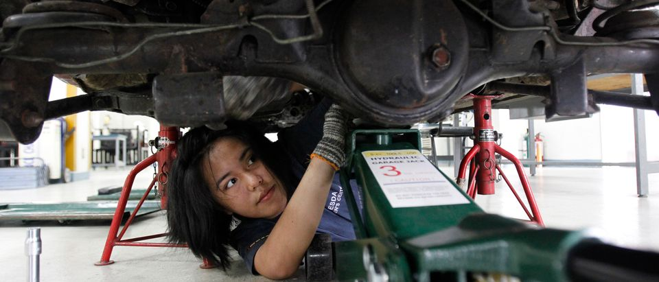 Vina Jane Aranas, 17, learns how to align the wheels of a car as part of her automotive training at the Technical Educational Skills and Development Authority (TESDA) in Taguig city, metro Manila November 5, 2013. Aranas took a 9-month automotive course after high school to improve her chances of employment, despite knowing it would lead her to a job in a male-dominated industry. The economic planning agency has said full-year GDP growth will likely be close to the top end of Manila's 6-7 percent goal, even though in October 2013, Philippines' unemployment rate slid to a 2-year low and poverty incidence in 2012 was 25.2 percent. REUTERS/Romeo Ranoco