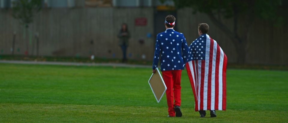 People wear the American flag as students and protesters gather ahead of the U.S. Republican presidential candidates debate in Boulder