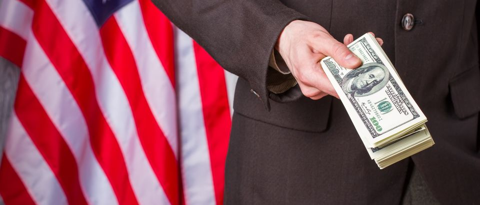 Man in a suit offers money in front of American flag (Photo: Shutterstock/ DenisProduction.com)