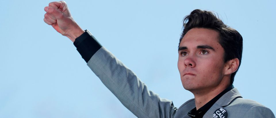 """David Hogg, a student at the Marjory Stoneman Douglas High School, site of a February mass shooting which left 17 people dead in Parkland, Florida, thrusts his fist in the air as he speaks during the """"March for Our Lives"""" event demanding gun control after recent school shootings at a rally in Washington, U.S., March 24, 2018. REUTERS/Jonathan Ernst - HP1EE3O1CC8FG"""