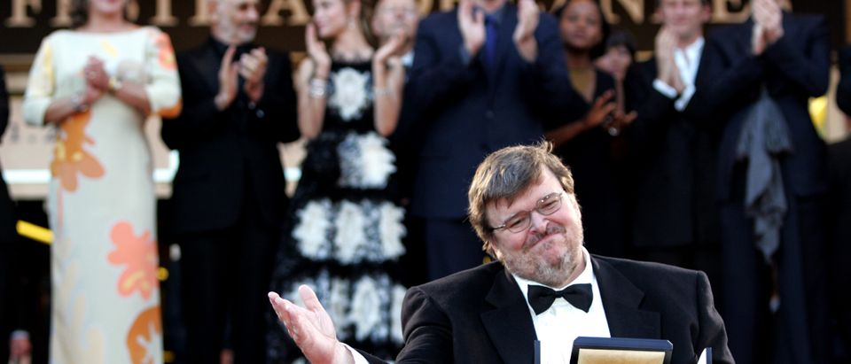 U.S. director Michael Moore (C) waves to the crowd as he holds the Palme d'Or for his documentary film 'Fahrenheit 9/11' as Jury President Quentin Tarantino (C Top) applauds with members of the jury during a special red carpet arrival at the 57th Cannes Film Festival, May 23, 2004. Seen on top row, from L-R: Kathleen Turner, Jerry Schatzberg, Emmanuelle Beart, Cannes Film Festival President Gilles Jacob, Tarantino, Edwidge Danticat, Benoit Poelvoorde, and Tilda Swinton. Pictures of the Year 2004 REUTERS/John Schults JES/AA - RP4DRIFUAYAA