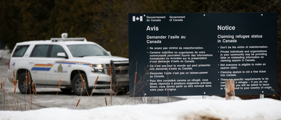 A RCMP vehicle is seen near a sign at the US-Canada border in Lacolle