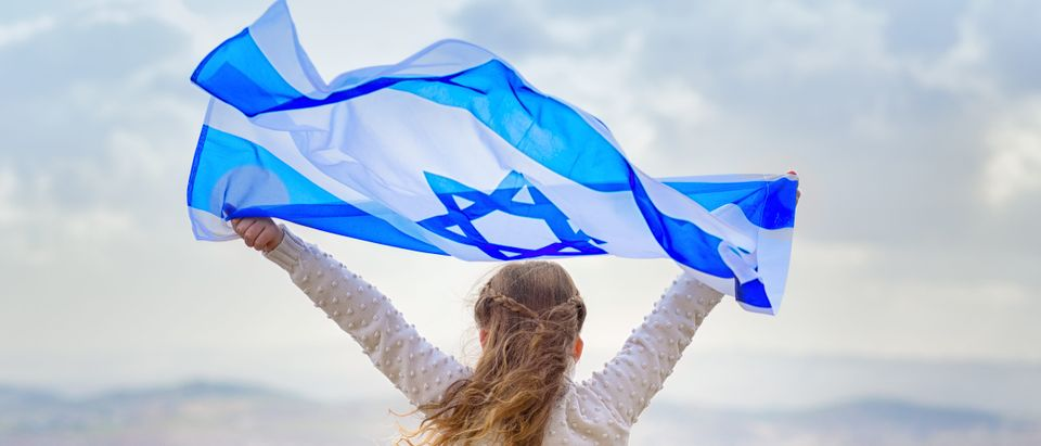 Little patriot jewish girl standing and enjoying with the flag of Israel on blue sky background.Memorial day-Yom Hazikaron, Patriotic holiday Independence day Israel - Yom Ha'atzmaut concept Shutterstock