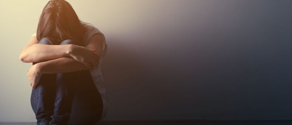 Teenager girl with depression sitting alone on the floor in the dark room. Shutterstock