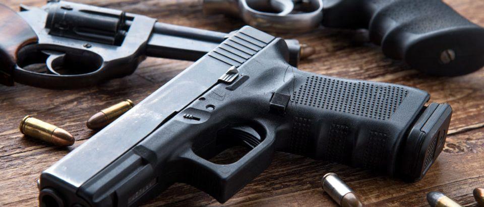 Gun with ammunition on wooden background. Shutterstock / Kiattipong
