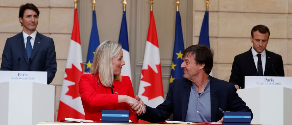 French President Emmanuel Macron and Canadian Prime Minister Justin Trudeau appaud as French minister of Ecology Nicolas Hulot and Canadian counterpart Catherine McKenna sign a ecology treaty at the Elysee Palace in Paris