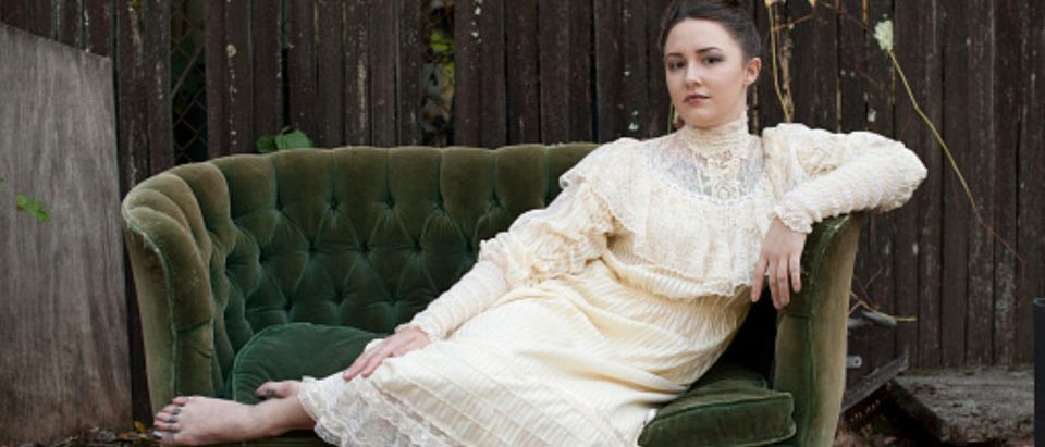 Caucasian woman wearing vintage gown on backyard sofa (Getty Images/Shestock)