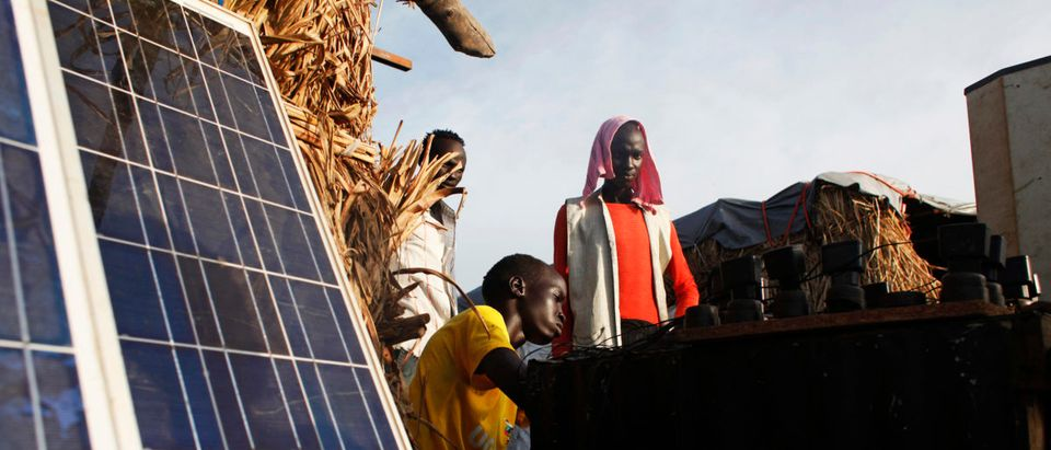 A youth displaced by the fighting charges batteries with solar panels at a makeshift shop in a camp for IDPs at the UN base in Bentiu