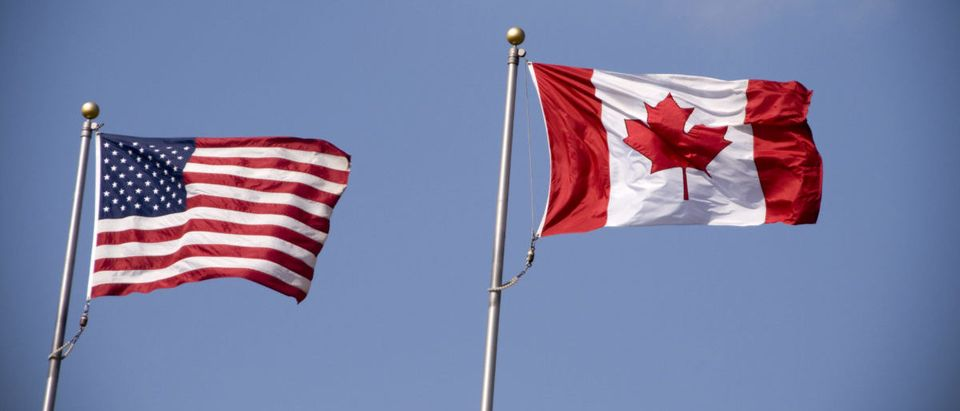 American and Canadian flags fly side by side. SHUTTERSTOCK/Stacey Newman