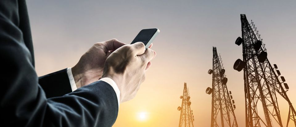 Businessman using mobile phone with Telecommunication towers with TV antennas and satellite dish in sunset -- ShutterStock -- Sasin Paraksa