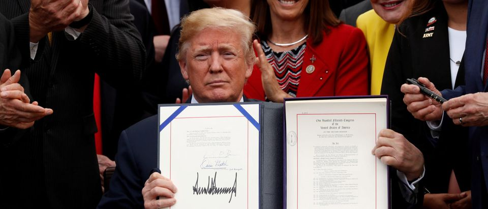 """U.S. President Trump displays the signed """"VA Mission Act of 2018"""" during signing ceremony at the White House in Washington"""