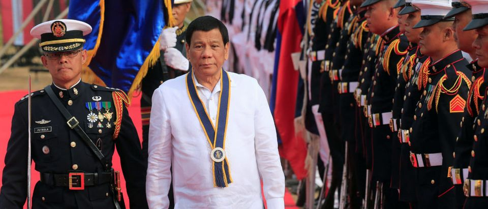 Philippine President Rodrigo Duterte reviews honour guards upon his arrival during the Philippine Navy's 120th anniversary in Metro Manila