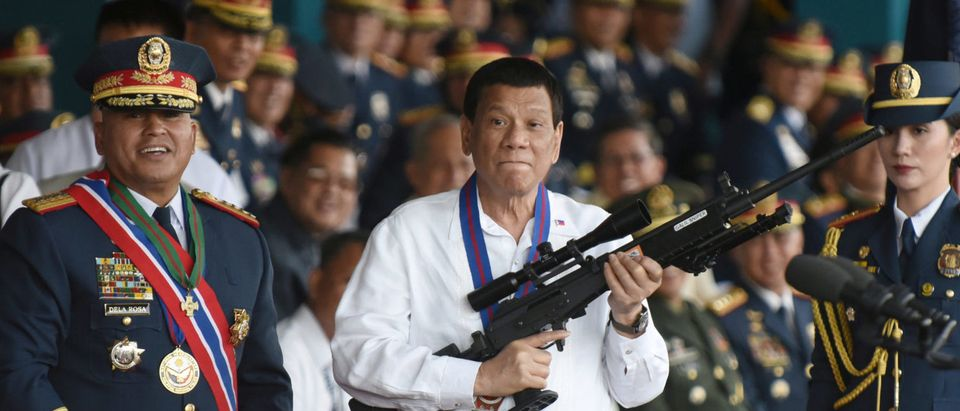 Philippine President Rodrigo Duterte holds a Galil sniper rifle next to outgoing Philippine National Police Chief Ronald Bato Dela Rosa during the National Police chief handover ceremony in Camp Crame