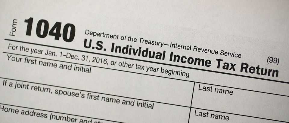 """MIAMI, FL - DECEMBER 22: A copy of a IRS 1040 tax form is seen at an H&R Block office on the day President Donald Trump signed the Republican tax cut bill in Washington, DC on December 22, 2017 in Miami, Florida. Kathy Pickering, vice president of regulatory affairs and executive director of The Tax Institute at H&R Block released a statement about the new tax bill saying, """" It's going to change the way you think about and plan your income taxes. You'll need to take a fresh look at your individual situation to know your outcome and new strategies to use to get the best tax outcome."""" (Photo by Joe Raedle/Getty Images)"""