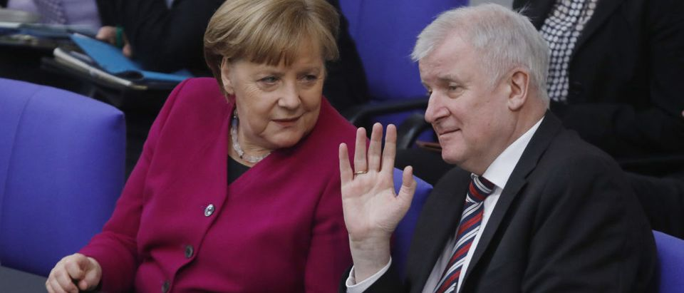 BERLIN, GERMANY - MARCH 21: German Chancellor Angela Merkel speaks to Interior Ministry, Horst Seehofer as she arrives to presents the first government declaration of her new government to outline the policy course for the next four years at the Bundestag on March 21, 2018 in Berlin, Germany. The new German government, once again a coalition of the Christian Democrats (CDU/CSU) and Social Democrats (SPD) was officially sworn in on March 14. (Photo by Michele Tantussi/Getty Images)