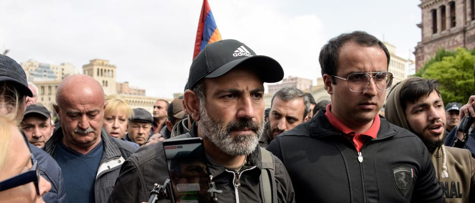 """Journalists and opposition supporters stand outside the hotel where Armenia's anti-government protest leader Nikol Pashinyan meets with Armenian Prime Minister Serzh Sarkisian who left shortly after the televised meeting began in Yerevan on April 22, 2018, denouncing the opposition's """"blackmail"""" after 10 days of mass demonstrations against an alleged power grab by Sarkisian. - Opposition supporters have criticised the 63-year-old leader over poverty, corruption and the influence of powerful oligarchs. Under a new parliamentary system of government, lawmakers elected him as prime minister last week. Constitutional amendments approved in 2015 have transferred power from the presidency to the premier. (Photo by Karen MINASYAN / AFP) / The byline of this picture has been modified in AFP systems as Karen MINASYAN instead of Vano SHLAMOV. Please immediately remove the erroneous mention from all your online services and delete it from your servers. If you have been authorized by AFP to distribute it to third parties, please ensure that the same actions are carried out by them. Failure to promptly comply with these instructions will entail liability on your part for any continued or post notification usage. Therefore we thank you very much for all your attention and prompt action. We are sorry for the inconvenience this notification may cause and remain at your disposal for any further information you may require. (Photo credit should read KAREN MINASYAN/AFP/Getty Images)"""