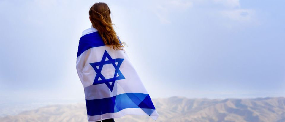 Little patriot jewish girl standing and enjoying great view on the sky, valley and mountains with the flag of Israel wrapped around her. (Shutterstock/Inna Reznik)