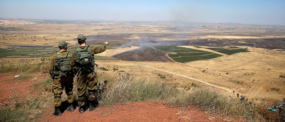 Israeli soldiers look at the Syrian side of the Israel-Syria border on the Israeli-occupied Golan Heights, Israel
