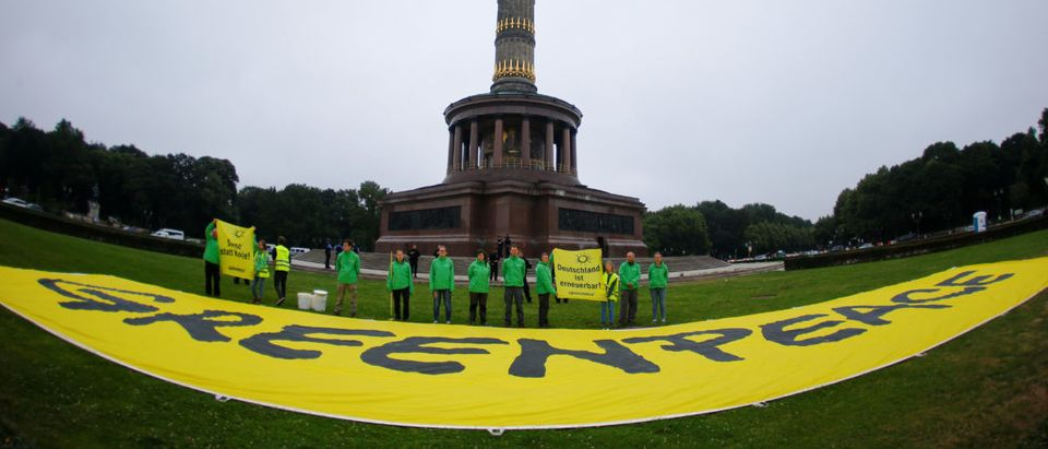 Greenpeace activists paint a street yellow in a protest to call for quick exit to coal fired power in Berlin