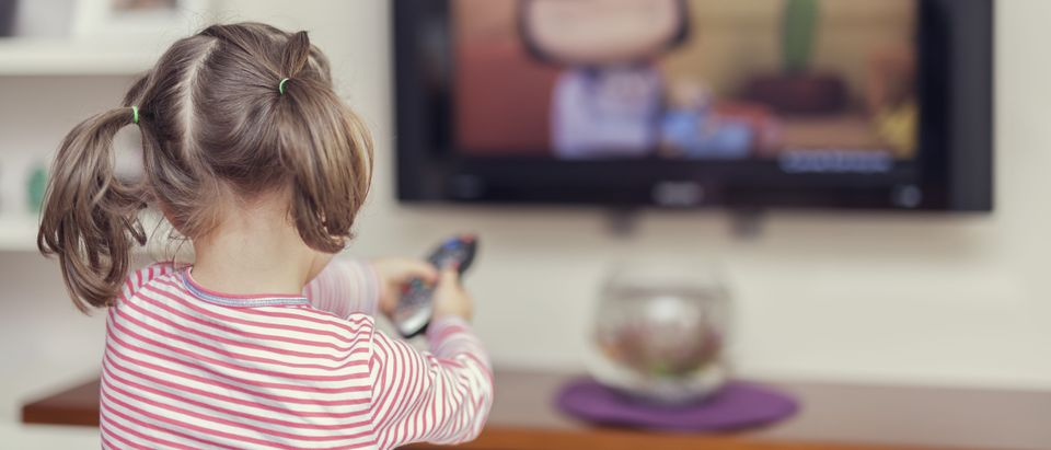 Little, cute girl pointing remote to control television at home. (Media credit Morrowind/Shutterstock)