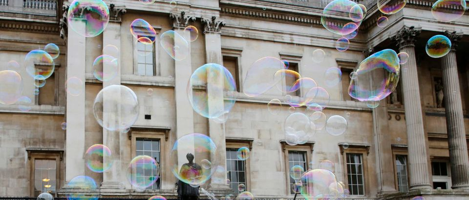 A tourist takes a selfie with soap bubbles made by a busker outside the National Portrait Gallery in central London