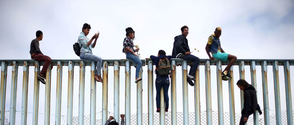 Members of a caravan of migrants from Central America climb up the border fence between Mexico and the U.S., as a part of a demonstration prior to preparations for an asylum request in the U.S., in Tijuana