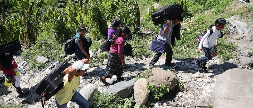 Undocumented Guatemalans carry their belongings after crossing the Guatemalan border into Mexico at the Suchiate River on August 1, 2013 in Talisman, Mexico. Thousands of Central Americans pass illegally into Mexico daily, many of them immigrants on the first leg of their long and perilous journey north towards the United States. Others stay in Mexico to work on seasonal farms before returning home. (Photo by John Moore/Getty Images)