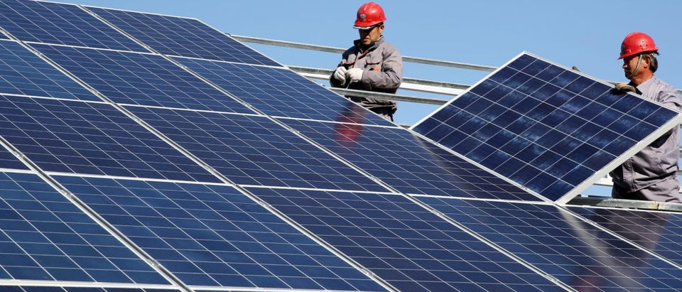 Workers install solar panels at a residential home in a village in Dongying