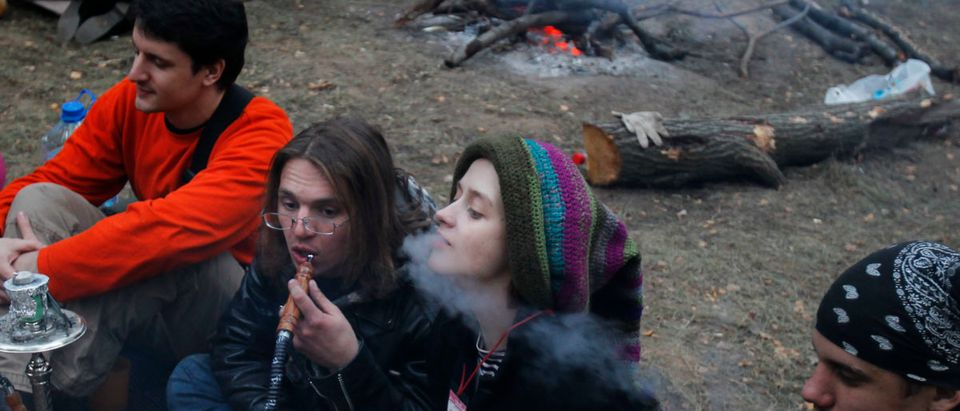 "People smoke a hookah as they sit by a fire during the ""Pustiye Holmi"" autumnal open-air hippie-style music festival outside the village of Koltsovo"