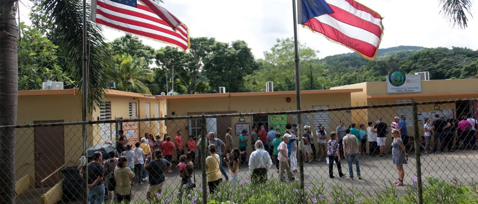 People stand outside a school turned into a polling station to cast their vote in the country's gubernatorial elections, in Guaynabo